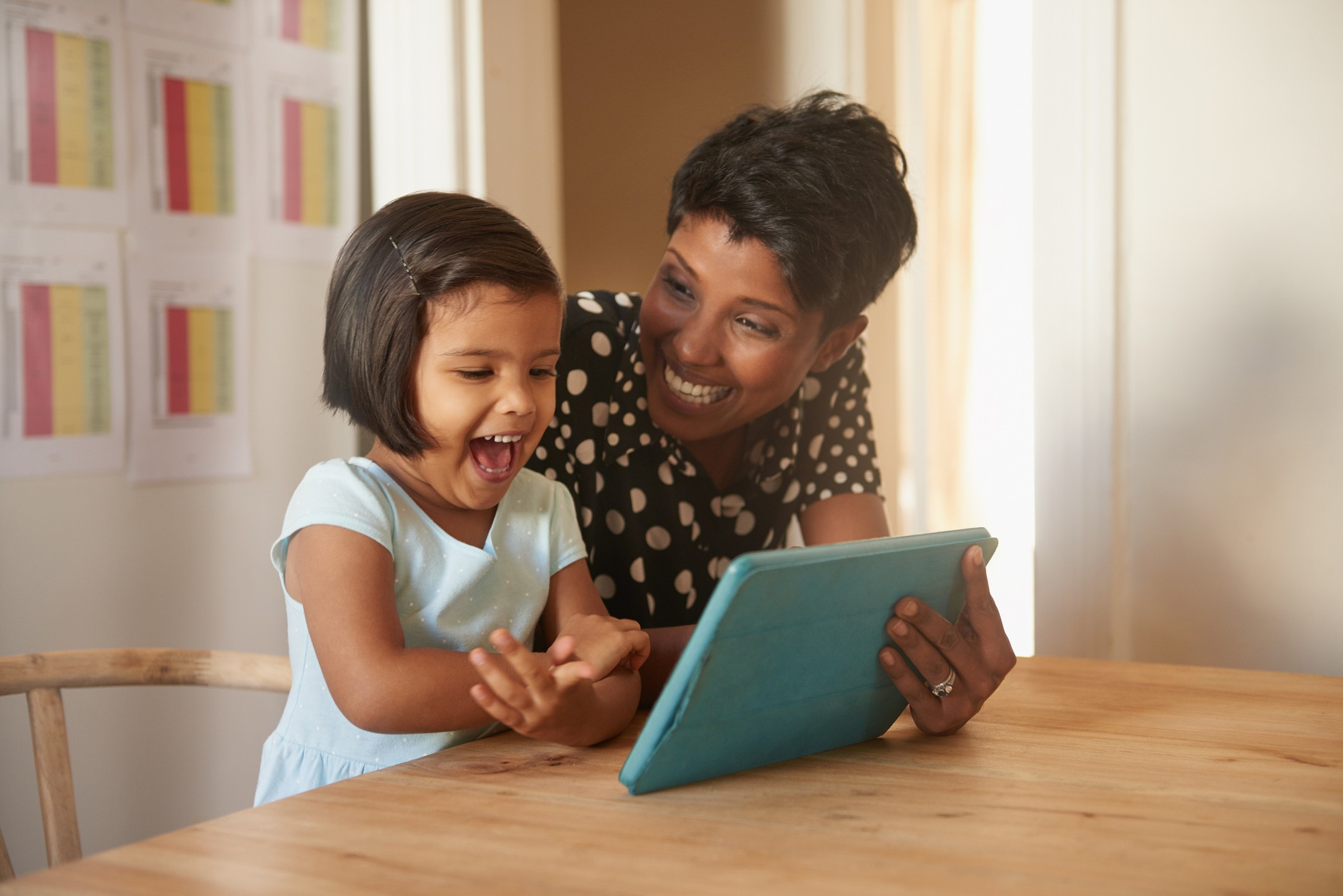 Excited child and parent on a tablet together.