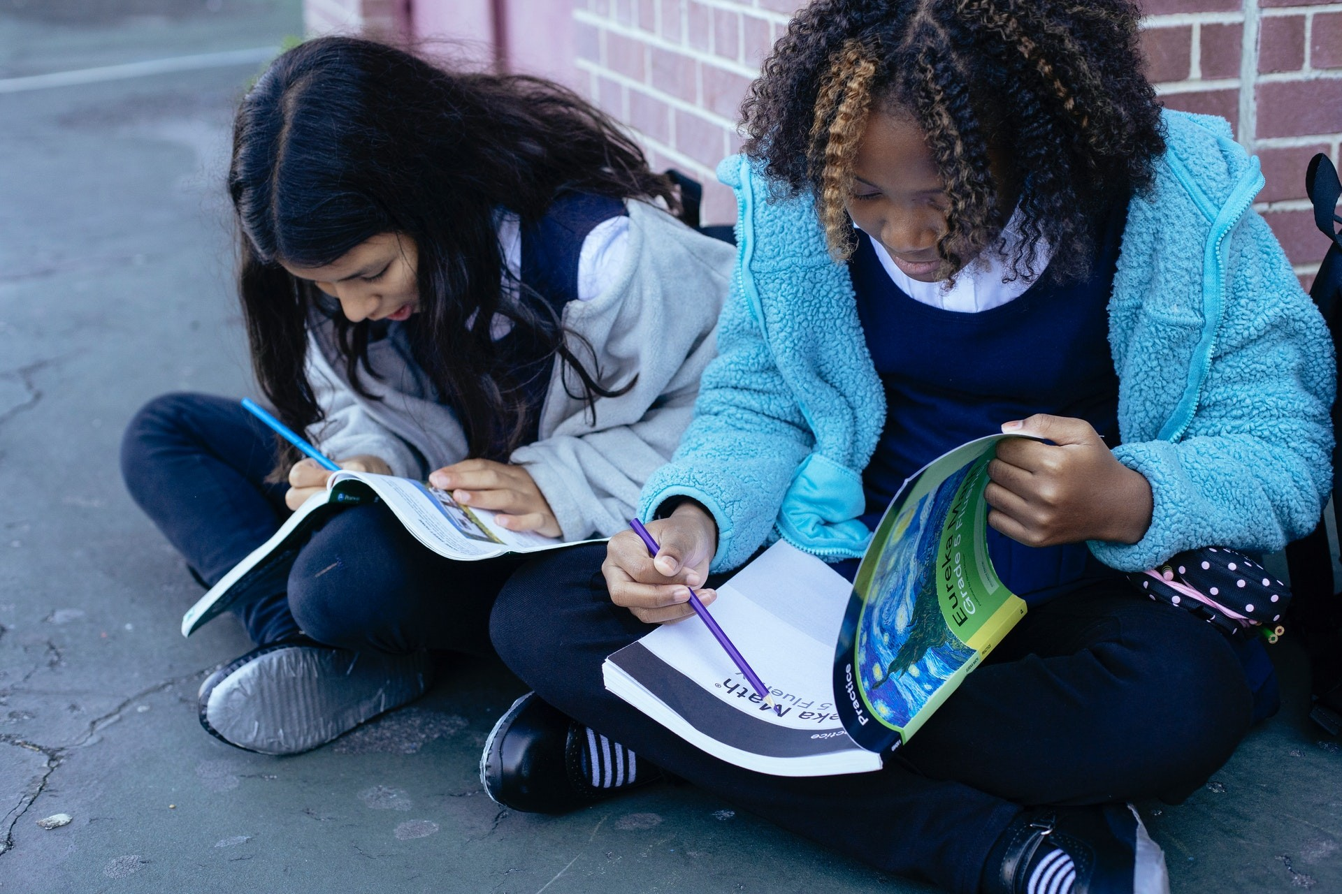 Two students sit outside against a brick wall, working in notebooks.