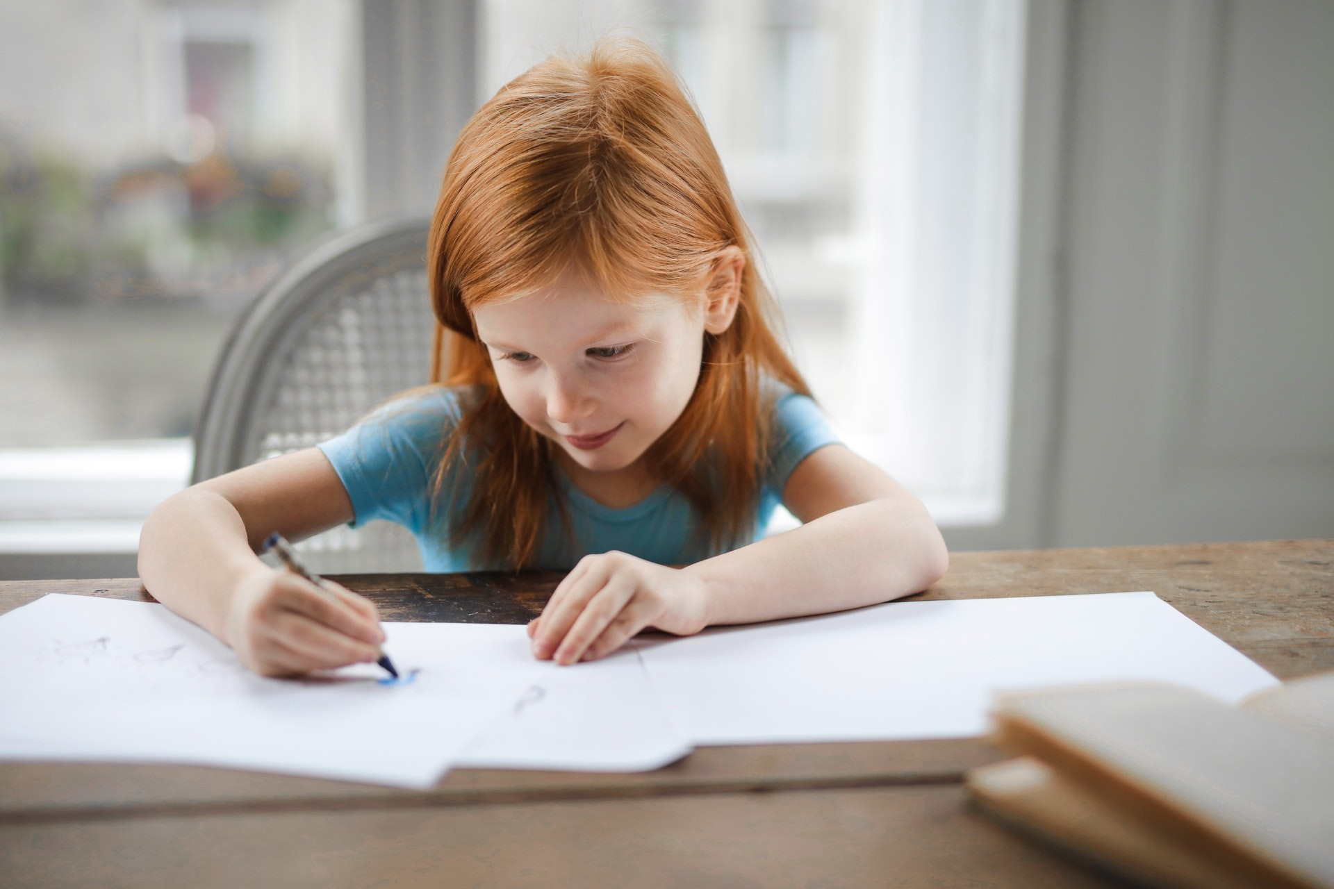 Young child sits at a table in front of a window while writing on a sheet of paper.