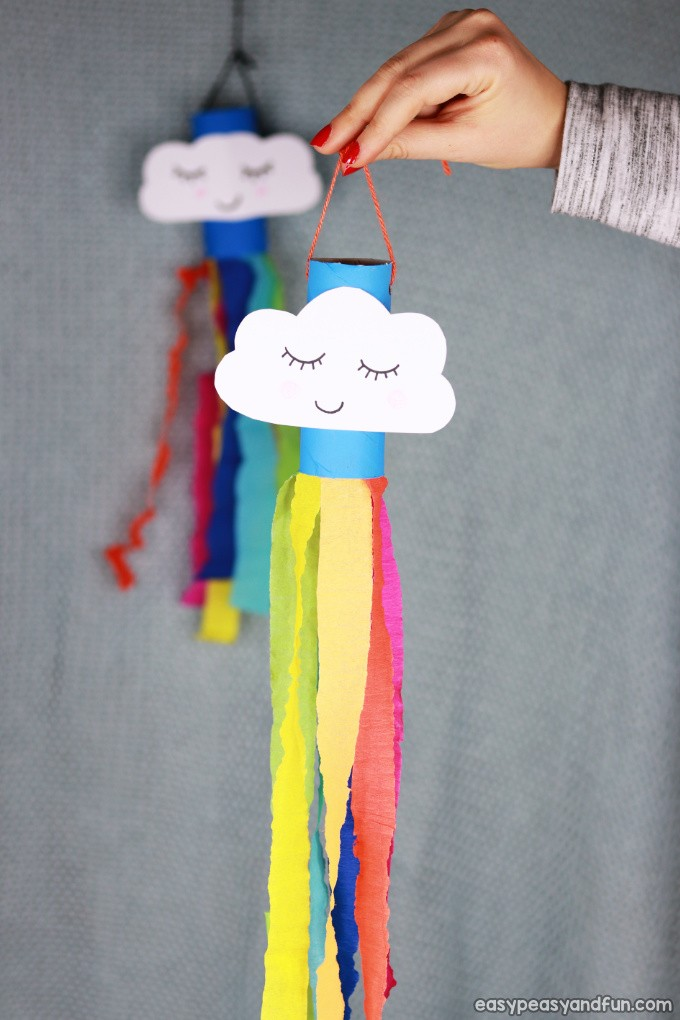 Rainbow windsock craft made from a blue painted toilet paper roll with a smiling cloud.