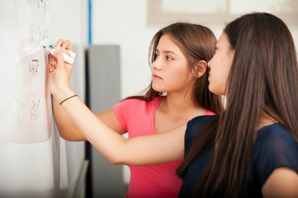Two girls solve math problems on a whiteboard in class.