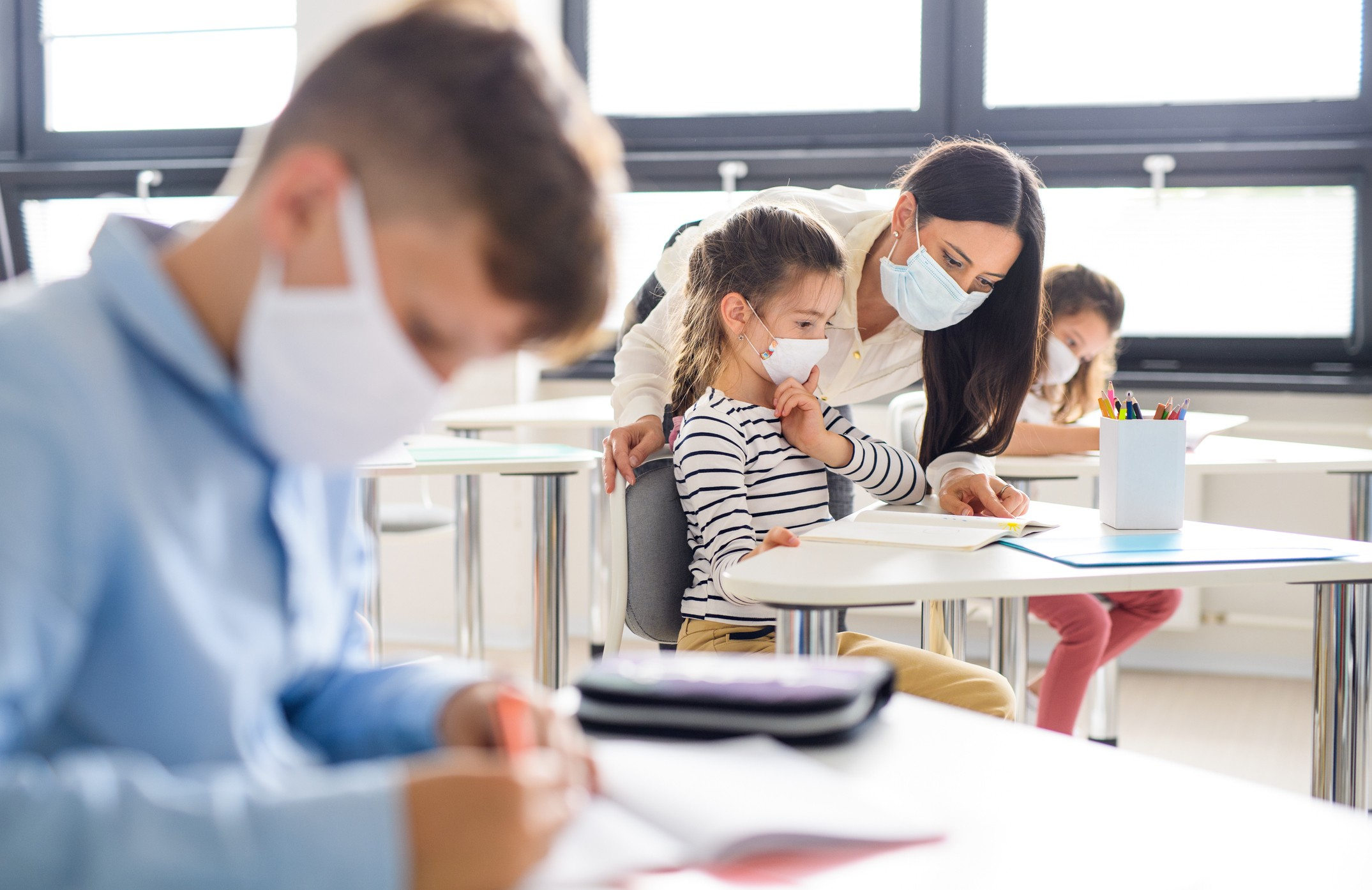 Three students sit socially distanced, wearing masks, in a classroom while a teacher helps one girl with her work.