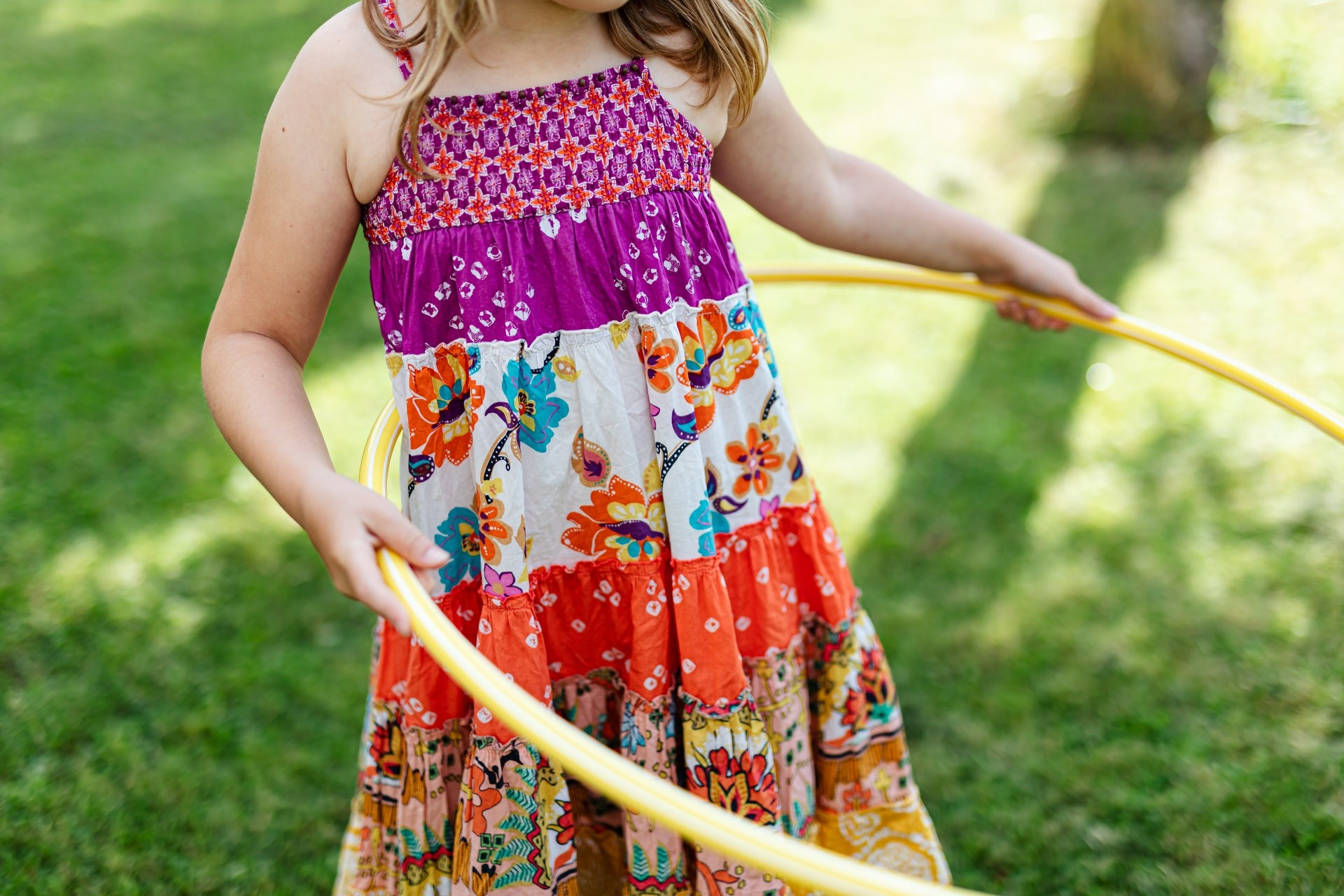 A young student plays with a hula hoop outside.