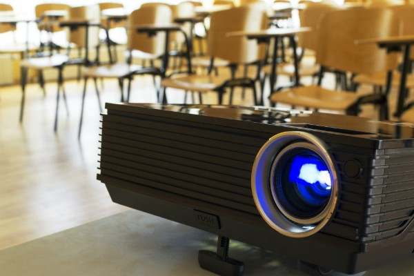 A projector set up in an empty classroom.