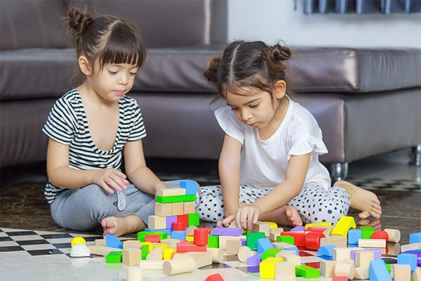 Two young children are sitting on the ground and building block