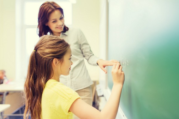 A female teacher is instructing student math on a blackboard