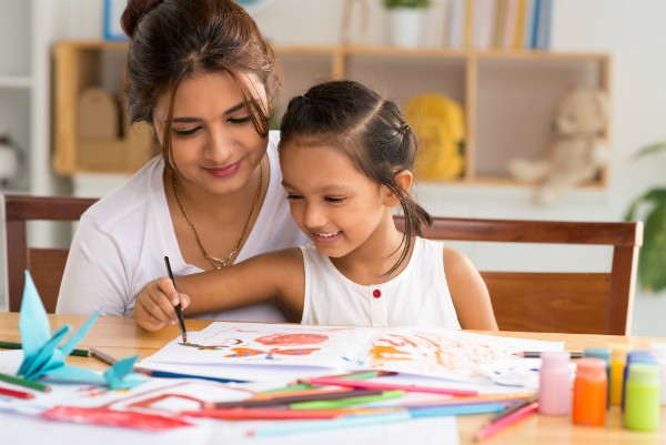 A mother and her daughter sit at a table at home coloring in a coloring book.