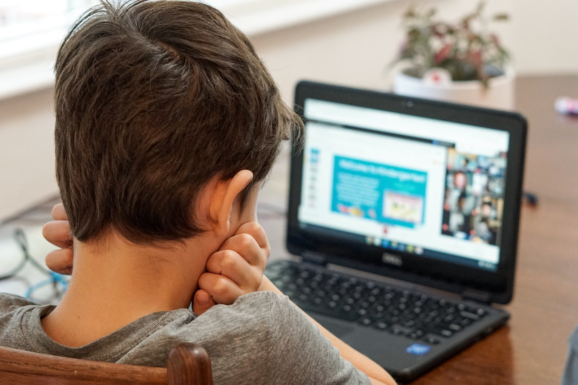 Boy sits at a table with his head in his hands, participating in a lesson with an online learning platform.