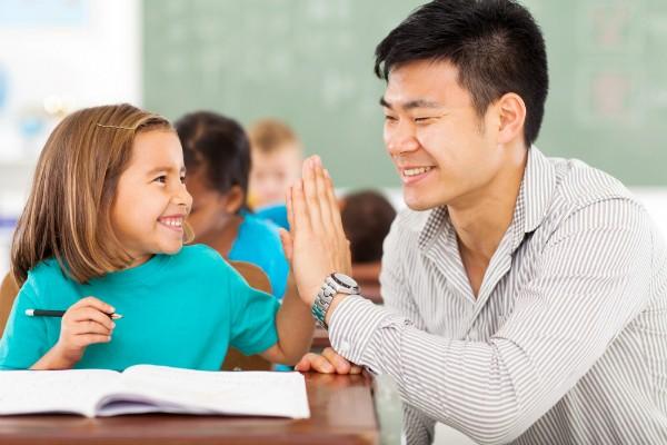 A teacher high-fiving an elementary school student.