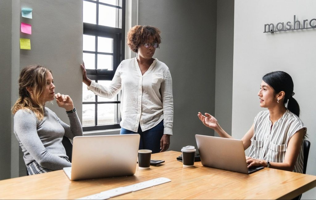 Three teachers are discussing classroom rules in a meeting room