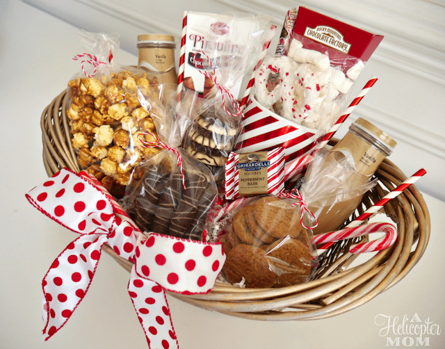 DIY wicker gift basket with a white and red polka-dotted ribbon and filled with holiday treats.
