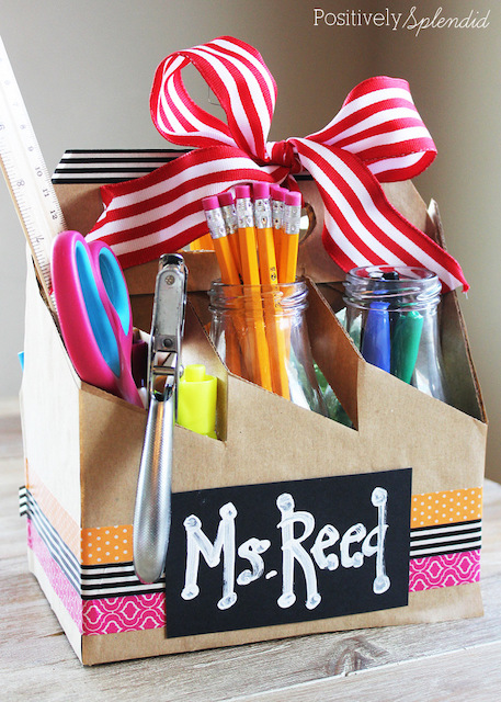 Cardboard supply kit with teacher's name written on the front and filled with pens and pencils.
