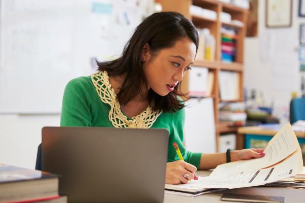 Teacher sitting at her desk and grading work