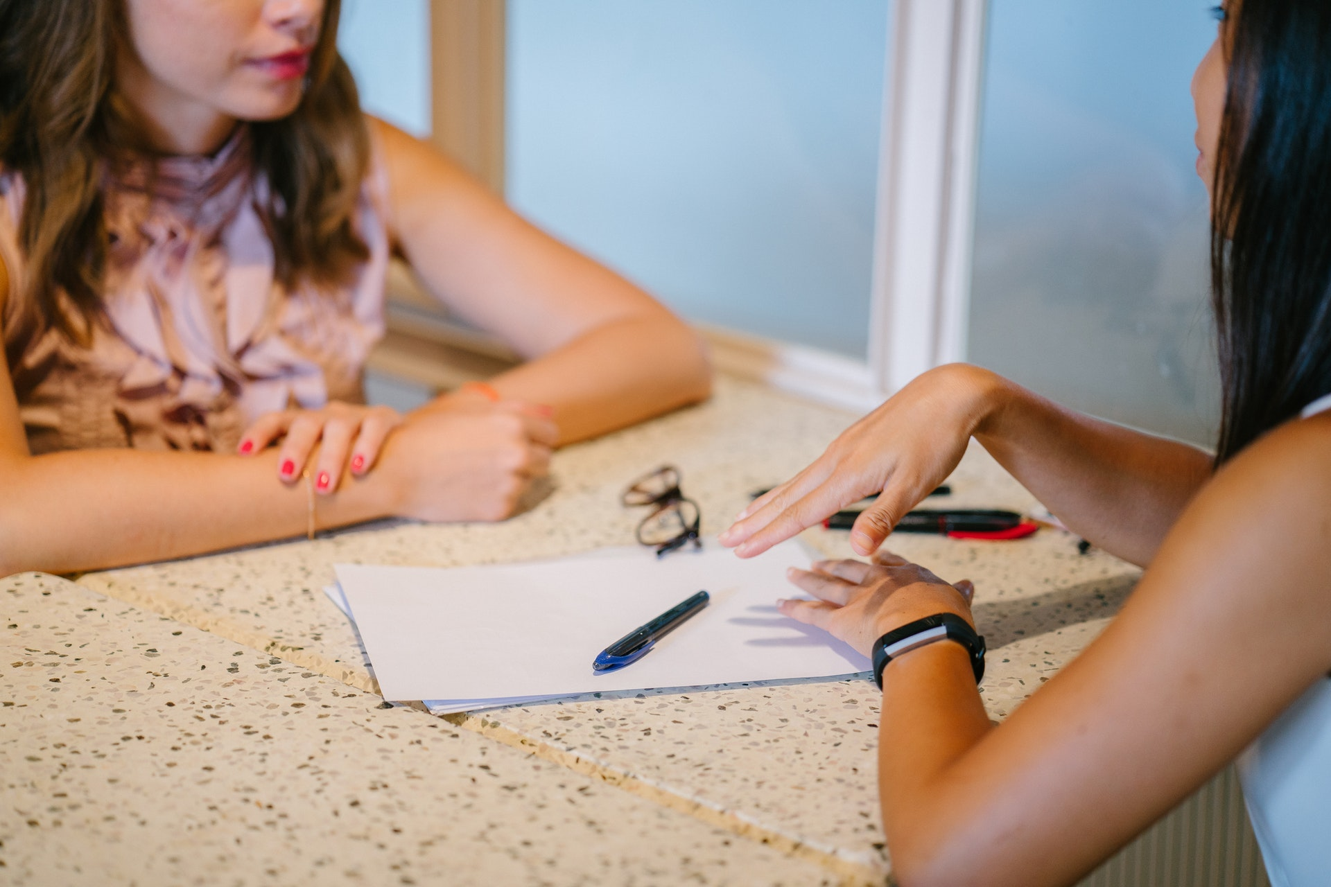 Two women sit across from a table talking to each other, with a pile of notes and a pen in between them.