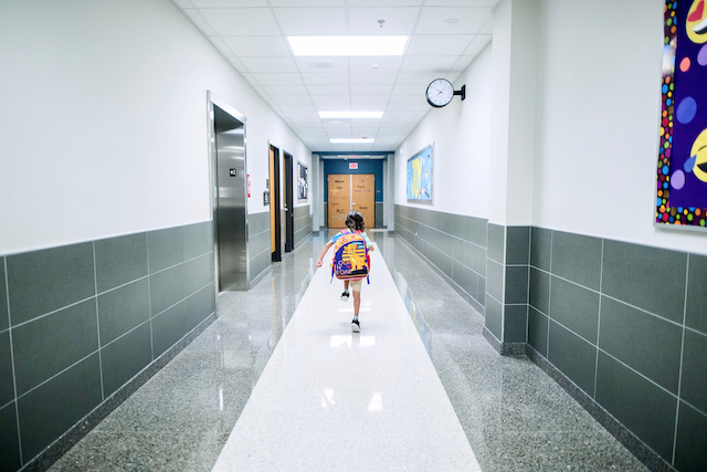 Student walking in empty school hallway