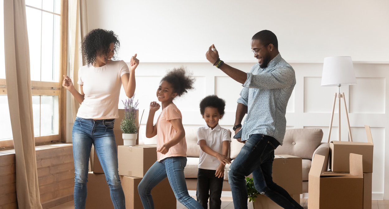 Parents dancing with their two kids in the living room