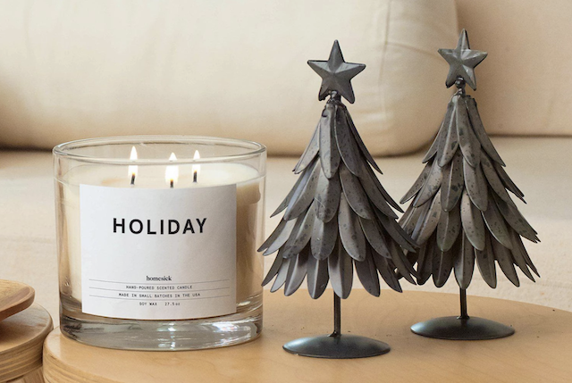 "3-wick candle with ""Holiday"" written on label, sitting beside two mini christmas tree models."