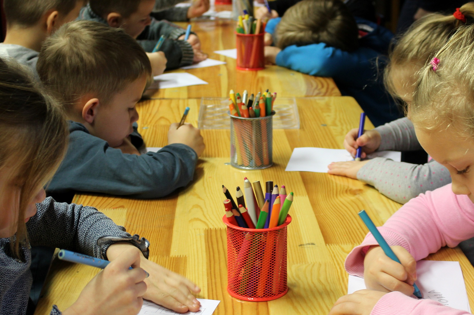 A group of kindergarten students sits at a long table, writing on paper with pencil crayons.