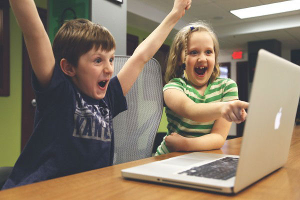 Boy and girl in front of laptop excited to play the best browser games