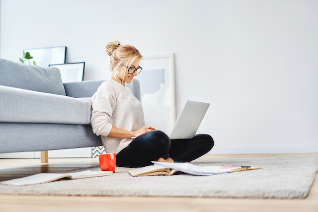 Woman sitting in front of her couch on laptop